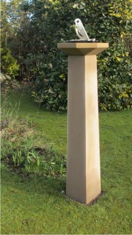 New sundial with brass gnomon as a garden bird and stone pedestal