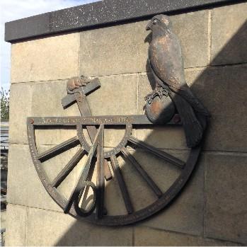 Sundial sculpture in bronze with sun symbols