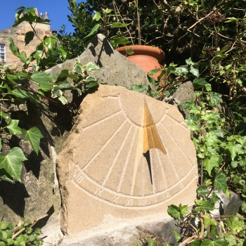 A stone sundial carved in rustic style for an Edinburgh garden